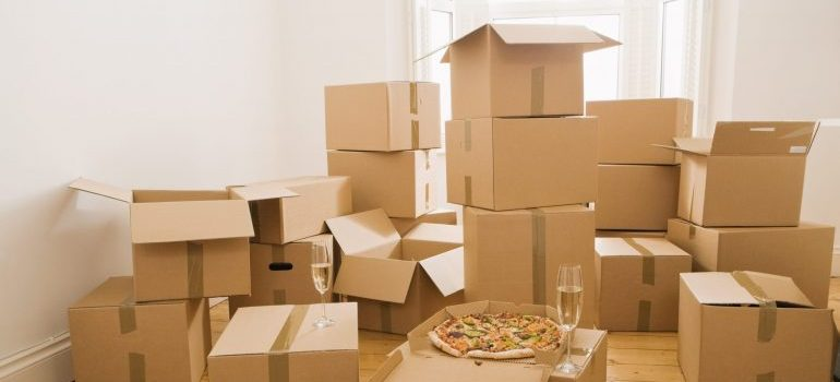 Moving boxes in a house with pizza and champagne on them.