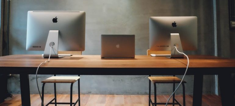 A desk with 3 computers - Lauderdale Lakes movers can help relocate your office