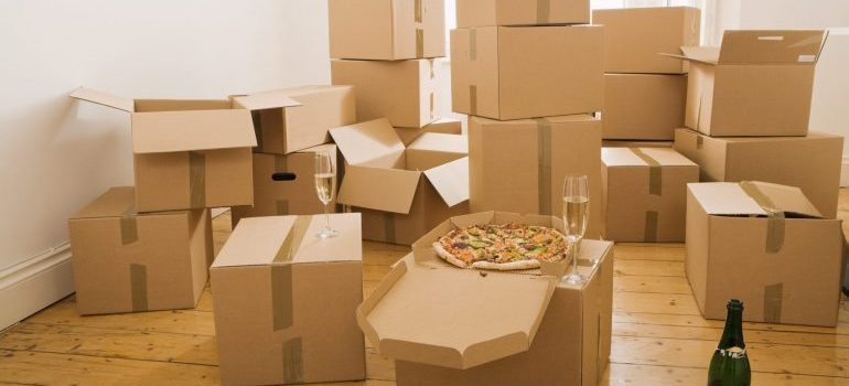 Pizza and champagne on top of cardboard boxes - The most comon packing mistakes