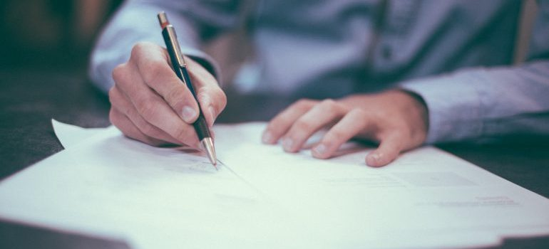 Man reading a contract before filing a moving insurance claim