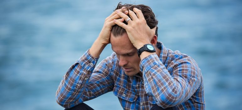 Man in plaid shirt pulling his hair - simplify last-minute move