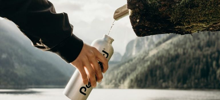 person filling a water bottle