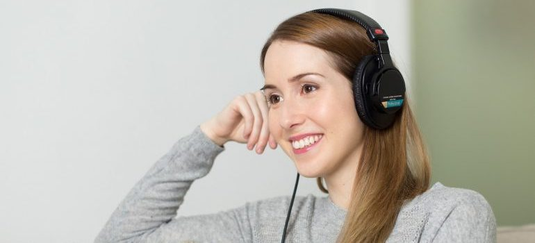 Woman with headphones on her ears listening to music