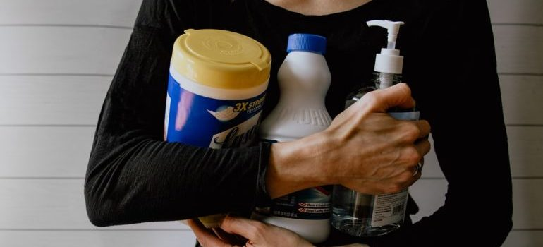 A woman holding cleaning items and supplies
