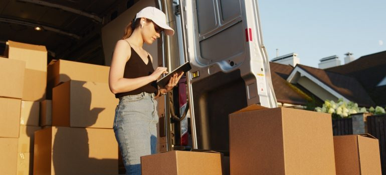 woman adding boxes to a moving truck