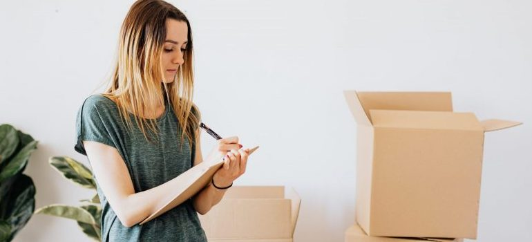 woman writing down, moving boxes behind
