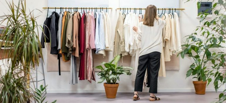 woman sorting clothes, plants around her