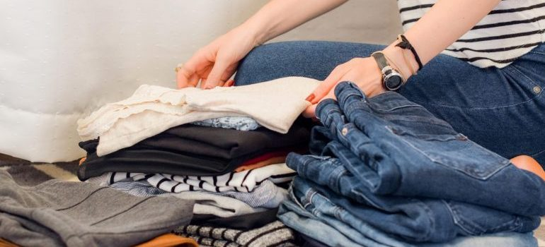 person folding unwanted clothes to donate after relocation