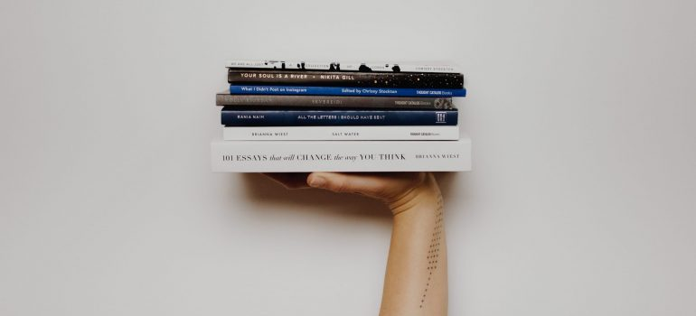 person holding a pile of books