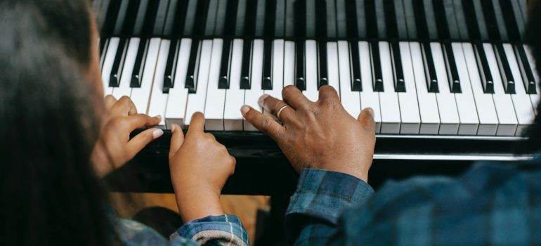 Two people playing a piano