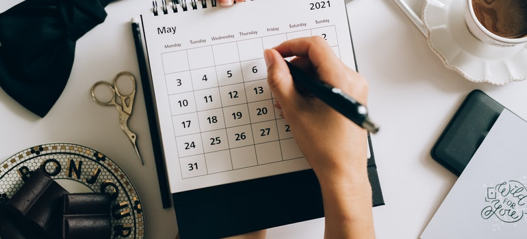 Woman writing on a calendar and choosing the cheapest time to move from Florida