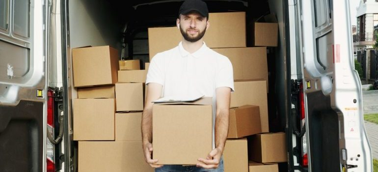 mover holding a box inside the moving van