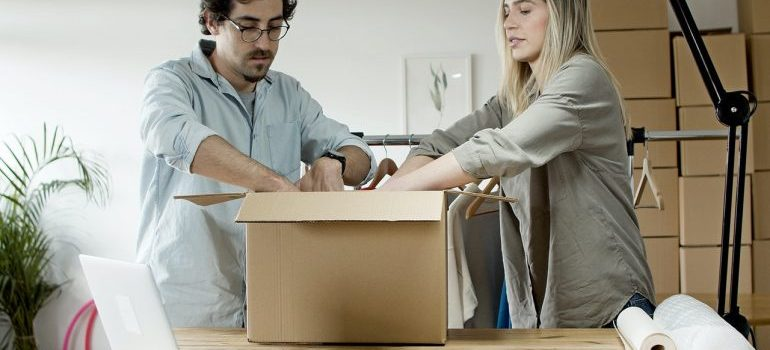 two professional packers filling a box