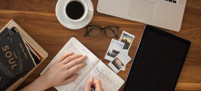 A notebook, a laptop and a cup of coffee - Plan how to move your home office