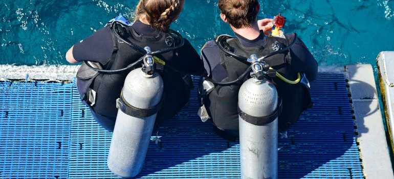 Two people next to a body of water with Scuba gear