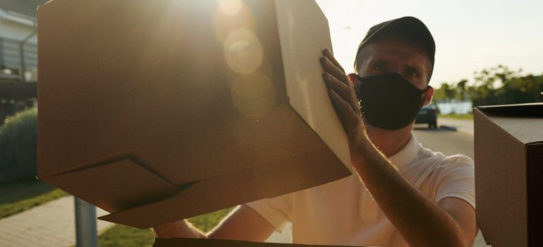 A mover with a face mask loading a box