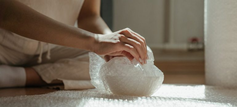 a woman packing a bowl in bubble wrap