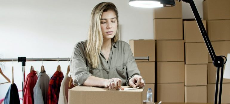 Woman packing things in the box for moving.