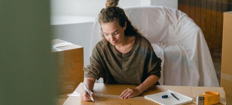Woman writing on a cardboard box
