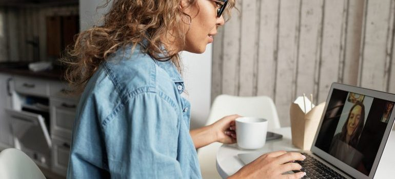 Woman drinking coffee and working on her laptop.