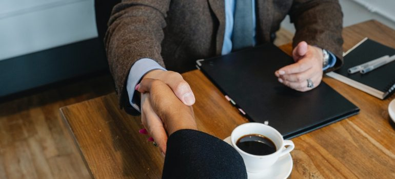 Two persons hands handshaking while making a deal at the table