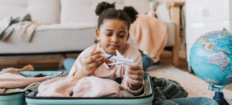 A little girl packing a suitcase and playing with an airplane toy.